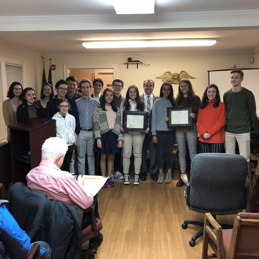 On the left with plaque, Gold Award Girl Scout Kimberly Rosell stands next to Mayor Chance Mullen. They are surrounded by staff members of the Pelham Examiner, who were also honored with a commendation.