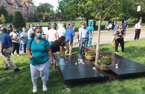 Wartburg staff placing flowers at the base of the Robert H. Coke Memorial tree.